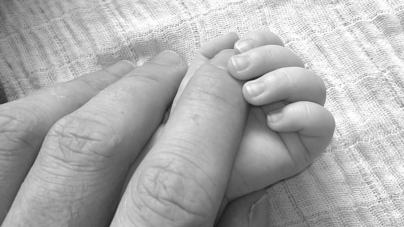 Photo d'illustration. Les mains d'un père et de son bébé.
