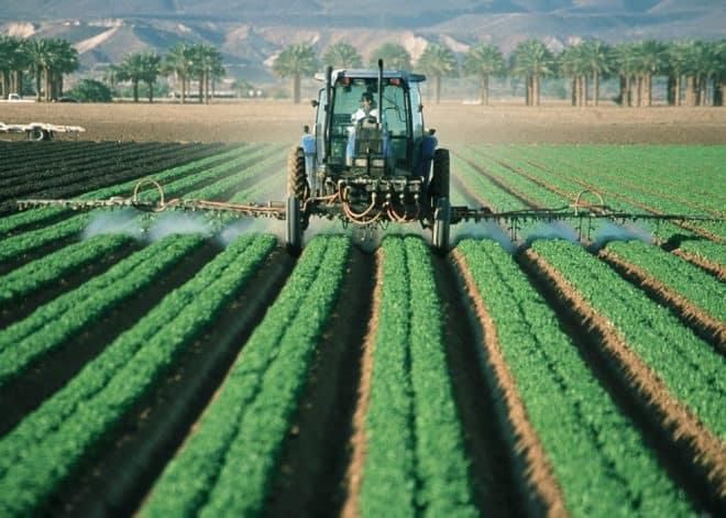 Un tracteur épandant des pesticides. Image d'illustration.