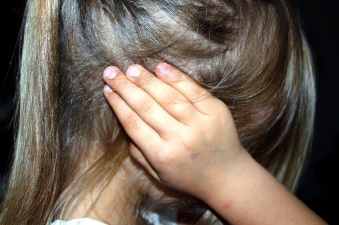 Une enfant qui se bouche les oreilles