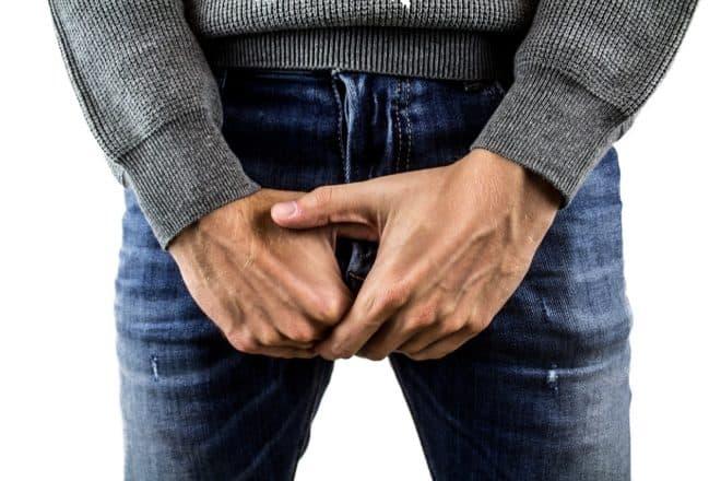 Un homme se cachant l'entrejambe avec ses mains. Image d'illustration.