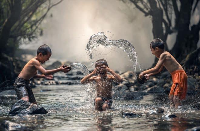 Illustration. Des enfants jouant dans une rivière.