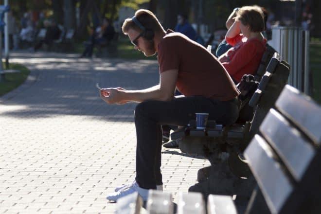 Illustration. Un homme fumant une cigarette dans un parc.