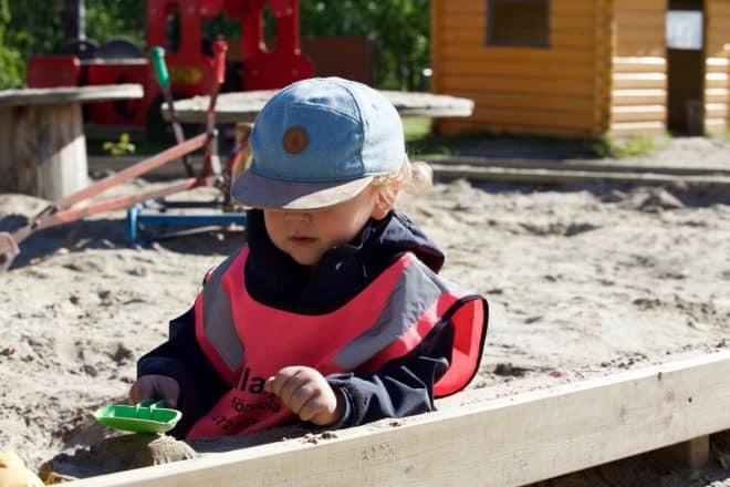 Un enfant jouant avec du sable à la crèche. Image d'illustration.