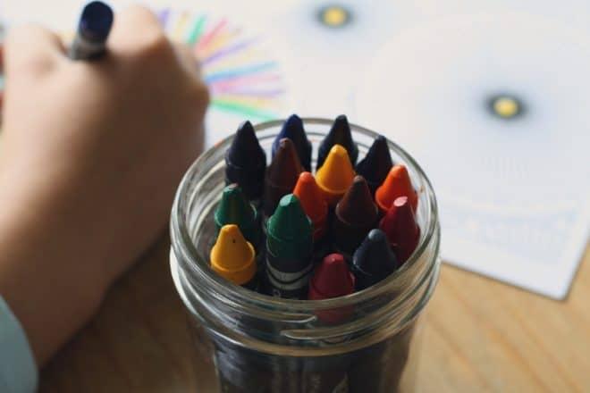 Un enfant, un crayon de couleur à la main, dans une garderie. Image d'illustration.
