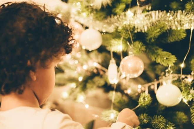 Illustration. Un enfant devant un sapin de Noël.
