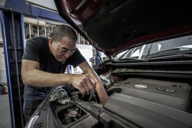 Un mécanicien inspectant une voiture. Image d'illustration.