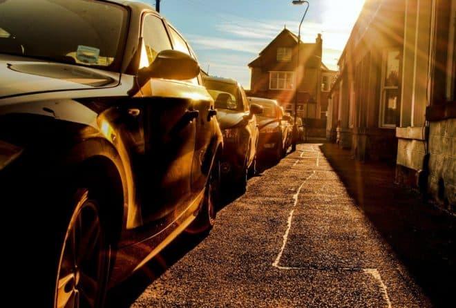 Illustration. Des voitures garées dans une rue.